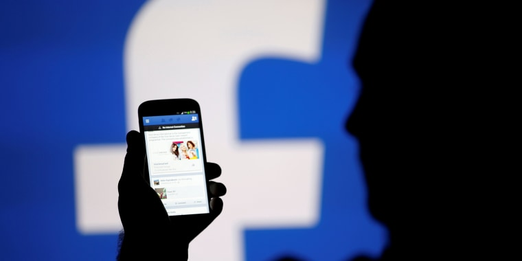 Image: FILE PHOTO: A man is silhouetted against a video screen with an Facebook logo as he poses with an Samsung S4 smartphone in this photo illustration taken in the central Bosnian town of Zenica