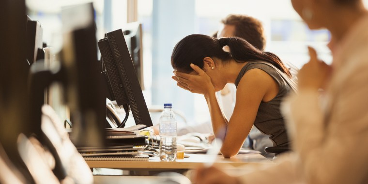 Image: Stressed woman sits with her head in her hands at an office desk