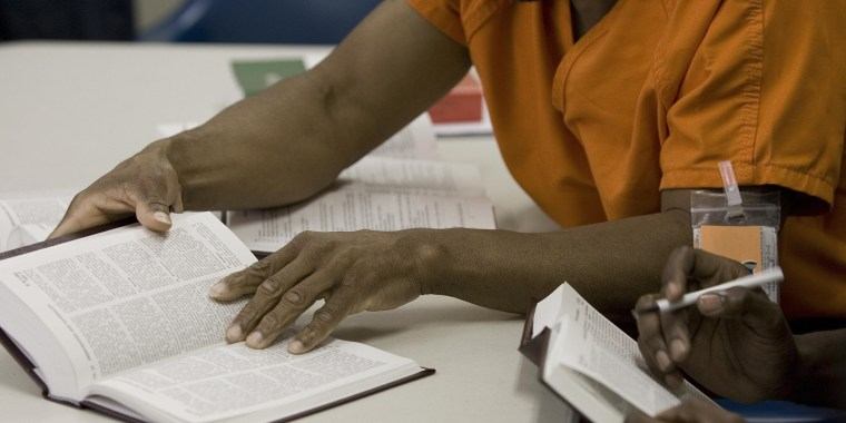 Image: Two male detainees read law books at the