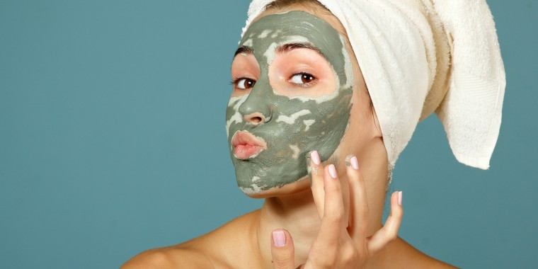 Girl applying facial clay mask.
