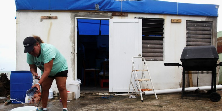 Image: Morales washes dishes in a bucket outside a her home, in Yabucoa