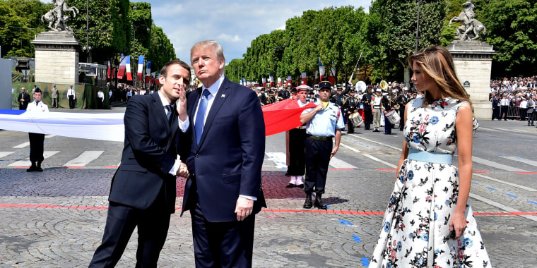 French President Emmanuel Macron shakes hands with President Donald Trump as first lady Melania Trump looks on after the Bastille Day military parade on the Champs Elysees avenue in Paris on July 14.