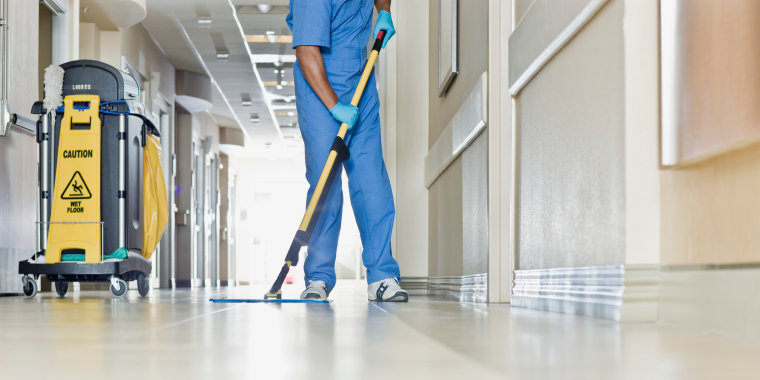Image: A janitor mops a hospital floor