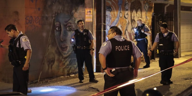 Image: Police search for evidence after a man was shot in the Little Village neighborhood of Chicago