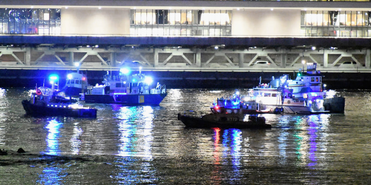 Image: Emergency responders work at the scene of a helicopter crash in the East River