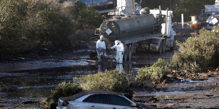 Image: Crews pump mud on Highway 101 after a mudslide