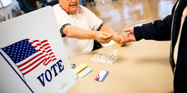 A poll worker hands out stickers to voters at a polling station on April 26, 2016 in Hanover, Pennsylvania.