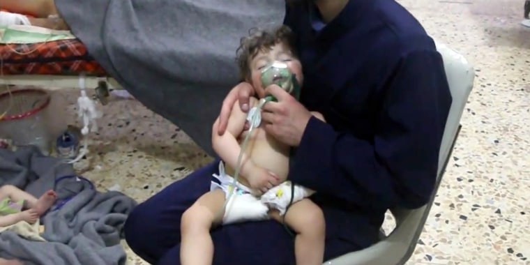 Image: A medical worker giving a toddler oxygen through a respirator