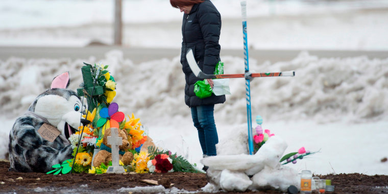 Image: A woman pays her respects at a makeshift memorial at the intersection of the fatal bus crash near Tisdale