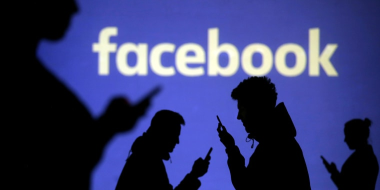 Image: mobile users are seen next to a screen projection of Facebook logo in this picture illustration