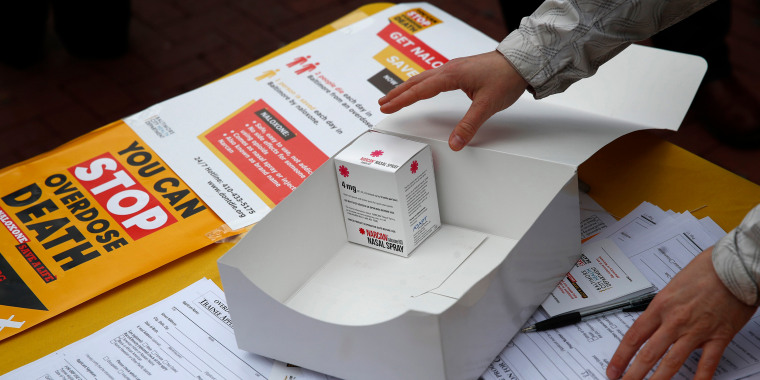 Image: A special projects director with the Baltimore City Health Department reaches for a package of Narcan nasal spray