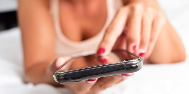 Image: young woman using a smartphone in bed