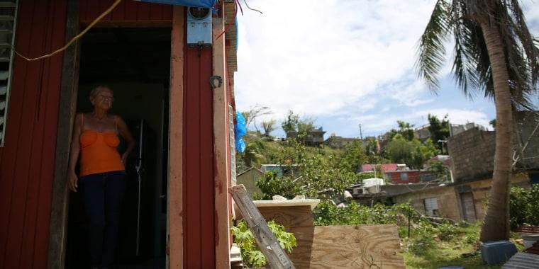 Image: Bexaida Torres stands in the door of what is left of her home after Hurricane Maria