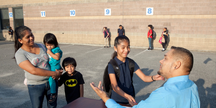 Image: A principal greets students at Leviton Dual Language Elementary School