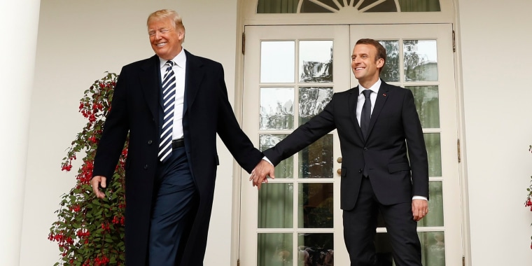 Image: U.S. President Trump and French President Macron hold hands as they walk down the colonnade past the Rose Garden at the White House in Washington