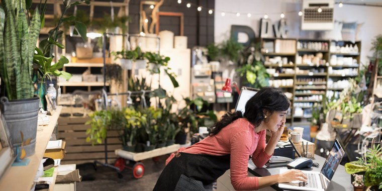 Image: Female shop owner talking on cell phone working at laptop at plant shop counter