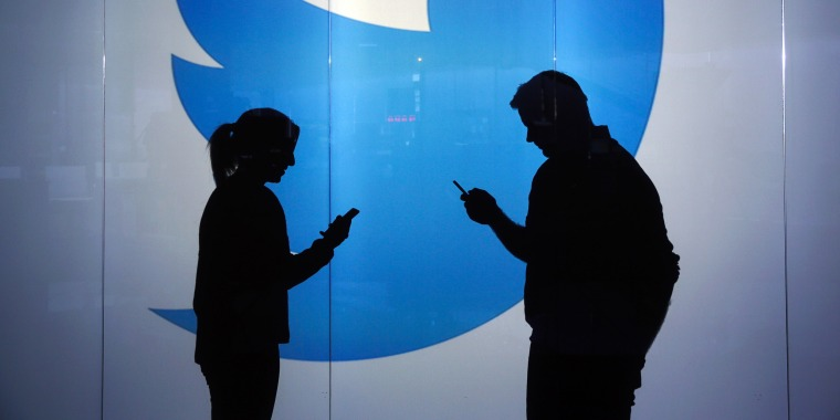 Image: People as silhouettes as they check mobile devices