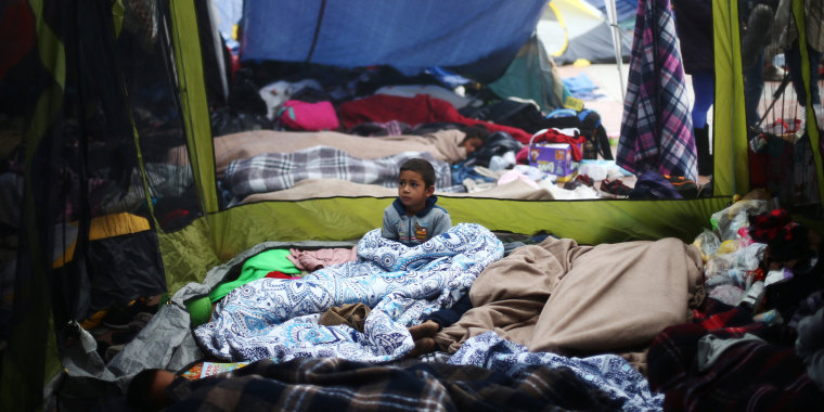 Image: A child traveling with a caravan of migrants from Central America sits at a camp near the San Ysidro checkpoint, after U.S. border authorities allowed the first small group of women and children entry from Mexico overnight, in Tijuana