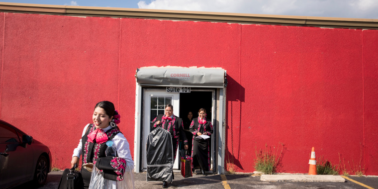 Image: Las Alte?as, an all-female mariachi group, leave their rehearsal space