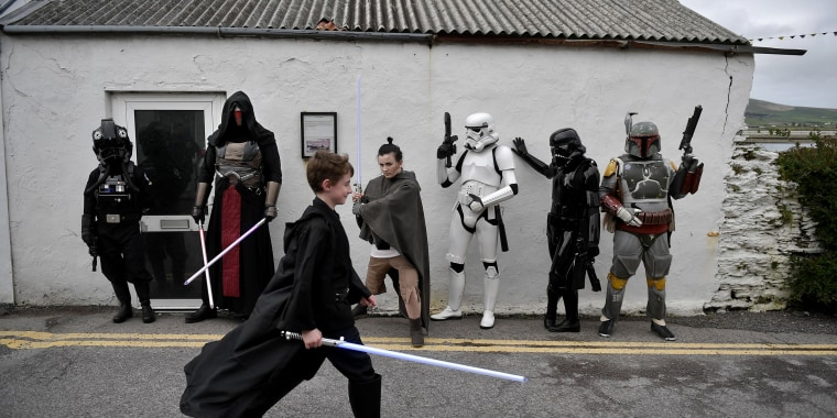 """Image: A young Star Wars fan walks past others in costume on """"May the Fourth be with you"""" day"""