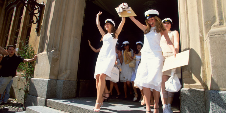 Women graduate in white dresses and matching white caps.