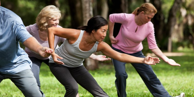 Image: People practice tai chi in park.