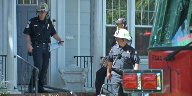 Image: Fire rescue workers stand outside the house of a man who died after a vape pen exploded