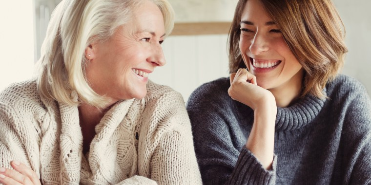 Image: Laughing mother and daughter in sweaters drinking coffee