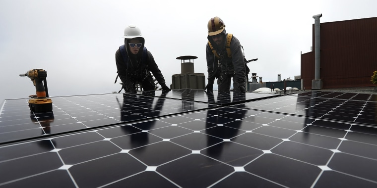 Image: Workers install solar panels on a roof