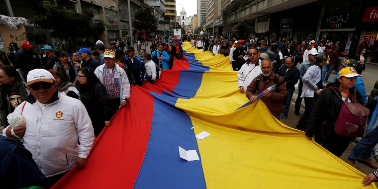 Image: Demonstrators carry a flag during May Day rally in Bogota