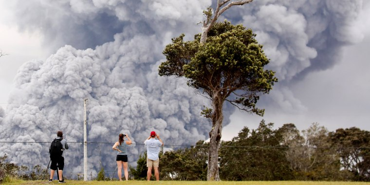 Image: People watch as ash erupt from the Halemaumau crater near the community of Volcano