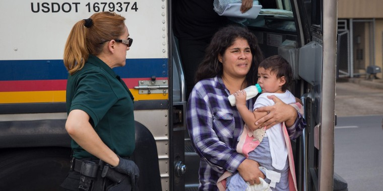 Image: A woman carries a baby as immigrants are dropped off at a bus station