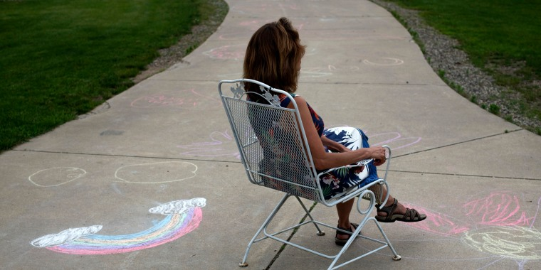 Image: Christine sits surrounded by chalk drawings from the unaccompanied migrant children she is currently fostering