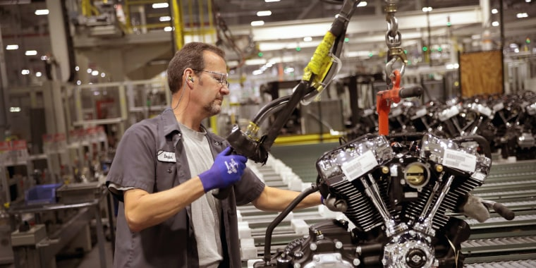 Image: A worker assembles a Harley-Davidson motorcycle engine