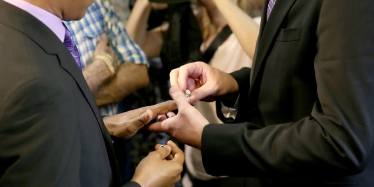 Image: Newlyweds exchange rings during a marriage ceremony