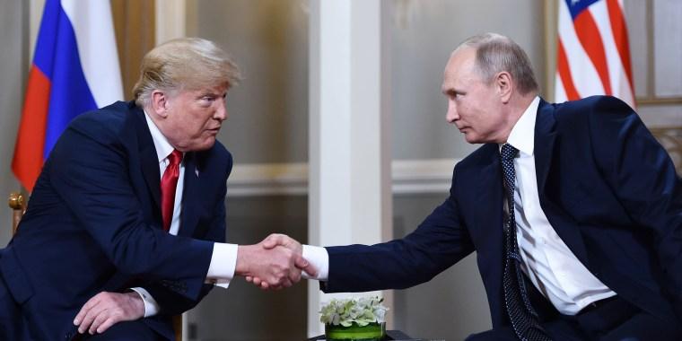 Image: Vladimir Putin  and Donald Trump shake hands before a meeting in Helsinki