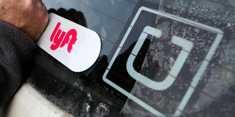 Image: A Lyft logo is installed on a Lyft driver's car next to an Uber sticker