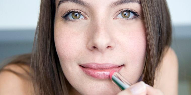 Woman applying lipstick, portrait, close-up