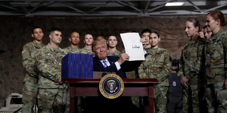 Image: President Donald Trump holds up the National Defense Authorization Act after signing it in front of soldiers at Fort Drum