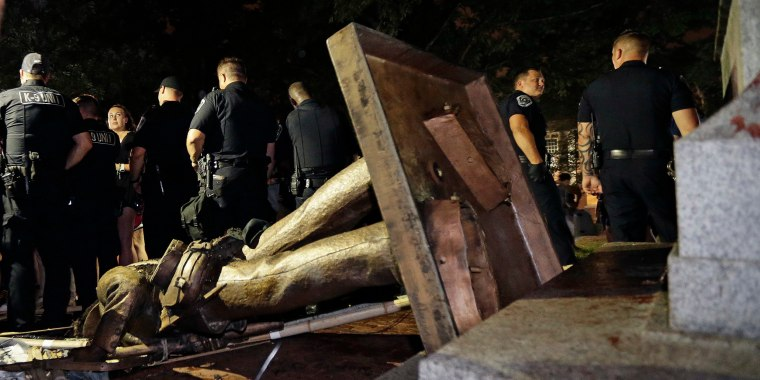 Police stand guard after the confederate statue known as Silent Sam was toppled by protesters
