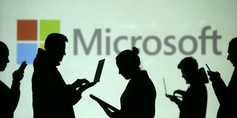 Image: Silhouettes of laptop and mobile device users are seen next to a screen projection of Microsoft logo in this picture illustration