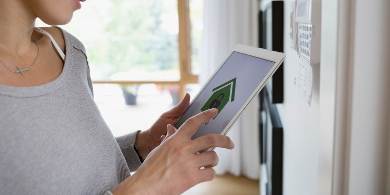 Image: Woman setting alarm with home security app on digital tablet