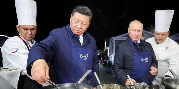 Image: Russian President Vladimir Putin and Chinese President Xi Jinping make pancakes