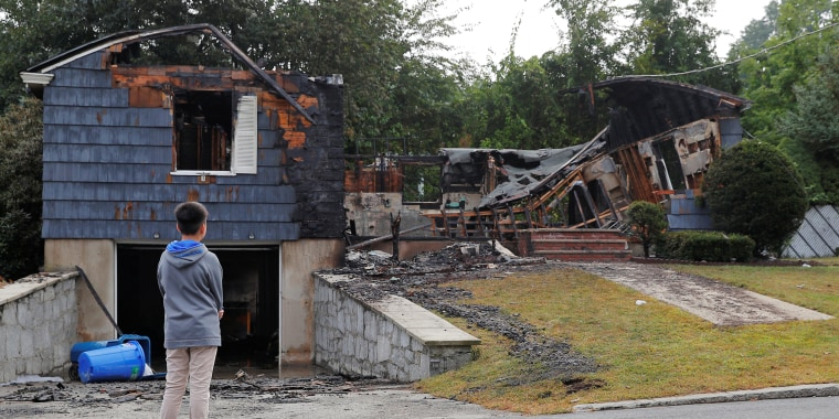 A neighbor looks at a home burned in a series of gas explosions in Lawrence