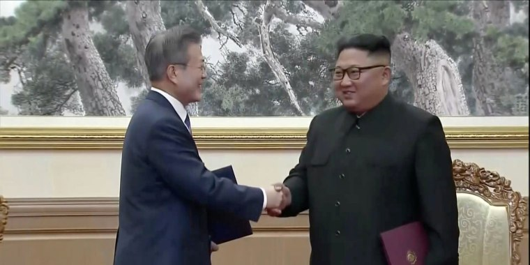 Image: South Korean President Moon Jae-in and North Korean leader Kim Jong Un shake hands after signing documents during the inter-Korean summit at the Paekhwawon State Guesthouse in Pyongyang