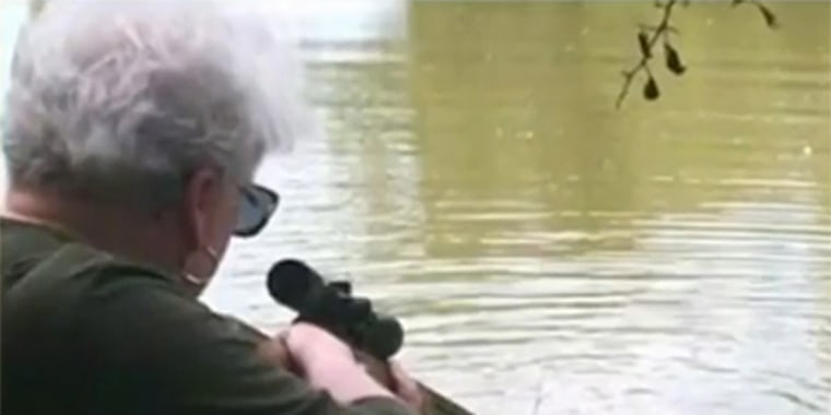 Judy Cochran takes aim at an alligator.