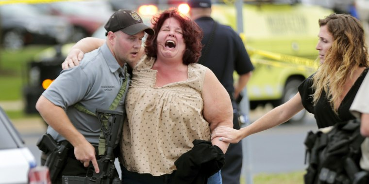 Image: A women is escorted from the scene of a shooting at a software company in Middleton, Wis.