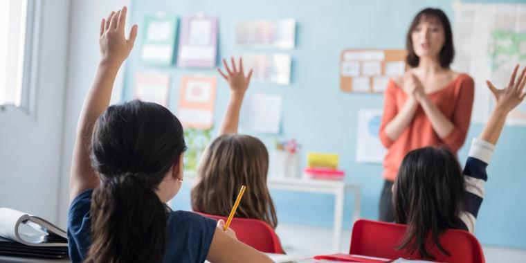 Girls raising hand for teacher in classroom