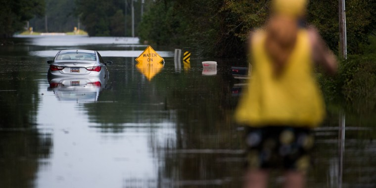 Image: A woman takes pictures of a disabled car in floodwaters caused by Hurricane Florence near the Todd Swamp
