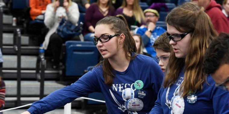 Image: Students representing the Neco Robo Knights help each other out during a round of the FIRST Tech Challenge robotics competition